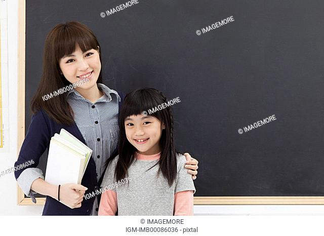 Young teacher and schoolgirl standing in the classroom and smiling