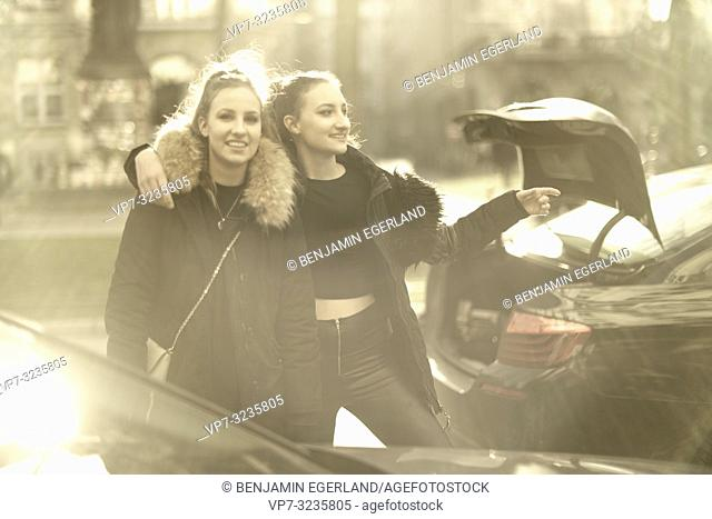 Two young sisters at street in city next to car with open trunk, wearing winter clothing, in Munich, Germany