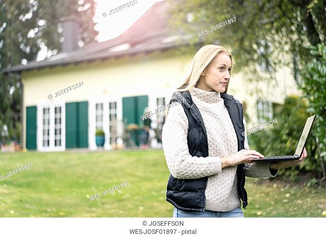 Young woman using laptop in garden