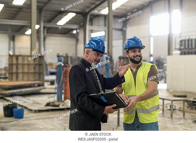 Businessman with folder talking to worker in factory
