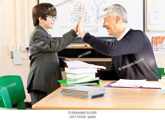 Teacher and middle school student high-fiving in classroom
