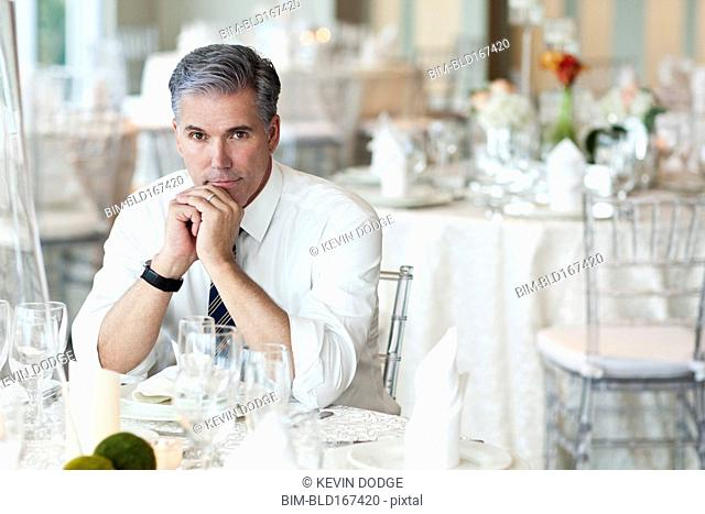 Caucasian businessman sitting in empty dining room