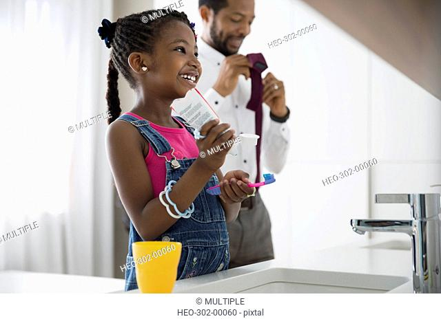Father and daughter getting ready in morning bathroom