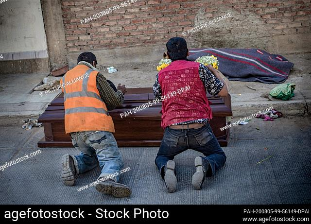 04 August 2020, Bolivia, Cochabamba: Two men are mourning in front of a coffin near the body of a deceased friend, Javier Ibanez