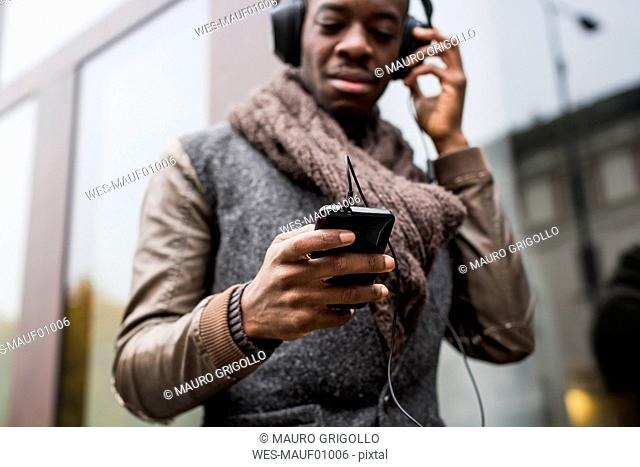 Bald man listening music with headphones looking at cell phone, close-up