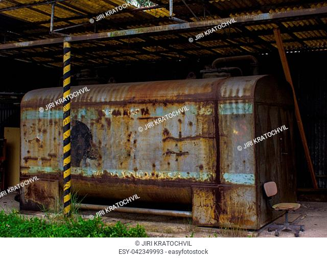 The old rusty gasoline tank stands under the shelter. In the foreground is grass
