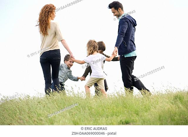 Family playing ring-around-the-rosy in meadow