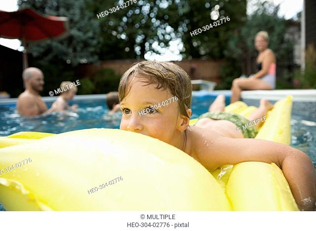 Carefree boy floating on inflatable raft in swimming pool