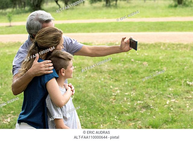 Family posing for a selfie outdoors