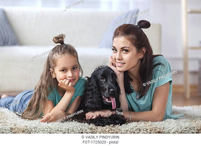 Portrait of mother and daughter lying with dog on rug at home