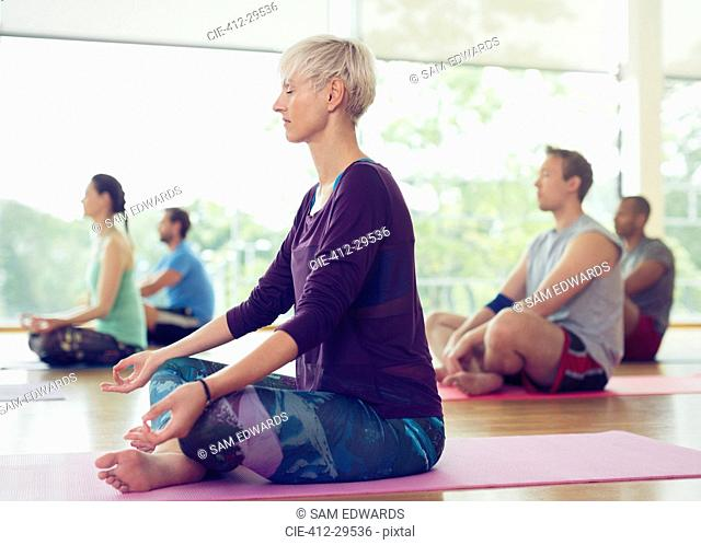 Serene woman in lotus position in yoga class