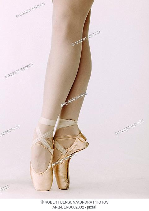 Low section of ballet dancer standing en pointe with slightly crossed legs
