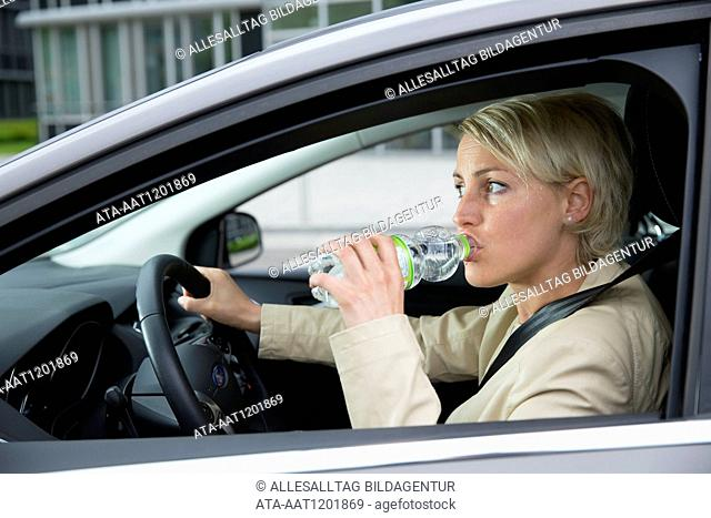 Female car driver is drinking a water