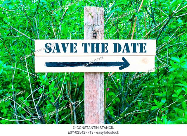 SAVE THE DATE written on Directional wooden sign with arrow pointing to the right against green leaves background. Concept image with available copy space