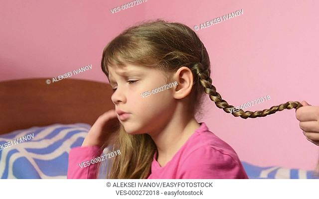 Mom braided pigtail daughter and kissed her on the cheek