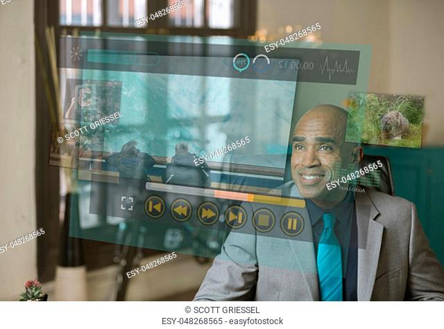 Smiling professional watching a futuristic video screen projection