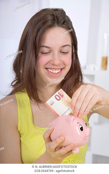 Smiling teenage girl in yellow putting a 10 euro banknote in her piggy moneybank