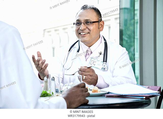 Hispanic man doctor in a lunch discussion with a colleague