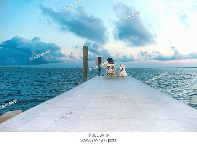Portrait of dog sitting on sea pier next to girl