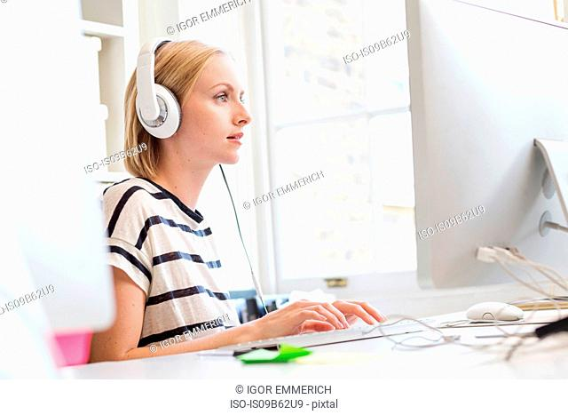 Female designer listening to headphones and typing at creative studio desk
