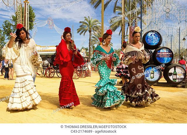 Young ladies wearing beautifully coloured gypsy dresses at the Feria del Caballo (Horse Fair) in Jerez de la Frontera. Cádiz province, Andalusia, Spain