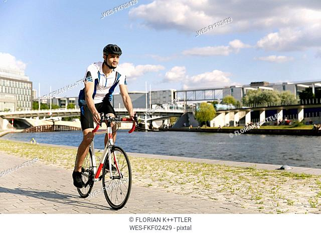 Young man riding bicycle at the waterfront in the city