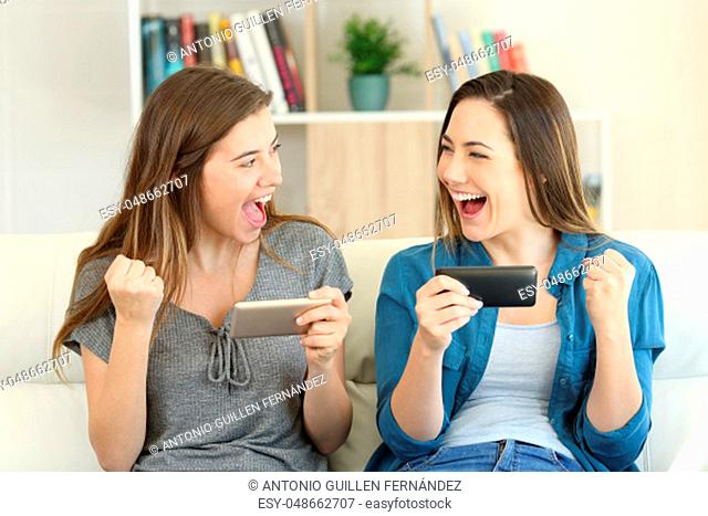 Excited friends playing online game and winning sitting on a couch in the living room at home