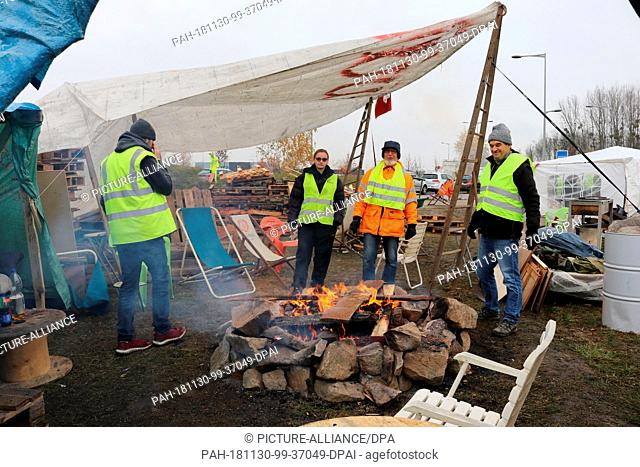"30 November 2018, France (France), Bernolsheim: Four """"yellow vests"""" warm themselves in their protest camp near Strasbourg at a campfire"