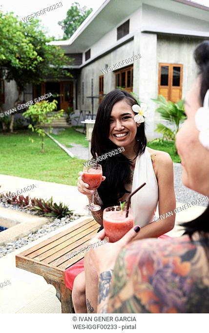 Portrait of woman with flower in her hair drinking a cocktail with friend in garden