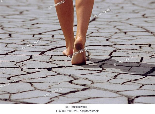 Woman's feet walking over cracked earth