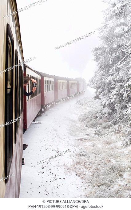 03 December 2019, Saxony-Anhalt, Wernigerode: A train of the Harzer Schmalspurbahnen (HSB) pulled by a steam locomotive travels through a snow-covered forest...
