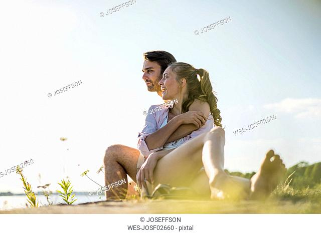 Happy couple relaxing at the riverside in summer