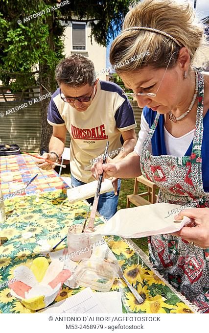 Amateur artista apply raku glaze on ceramic objects
