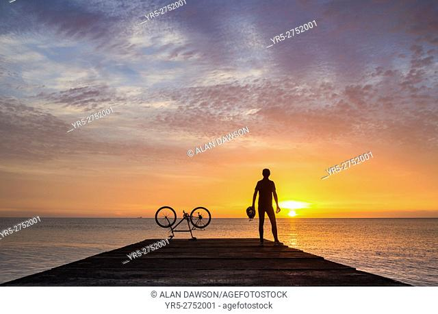 A mountain biker watches the sun rise over the North sea on a calm and tranquil morning at Seaton Carew, north east England, United Kingdom