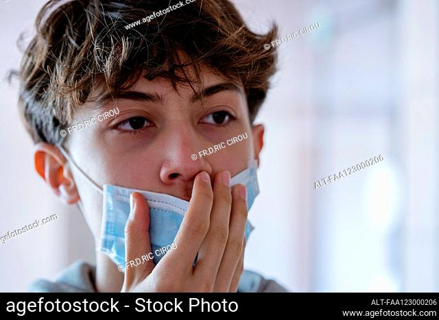 Close up of teenage boy wearing blue surgical mask