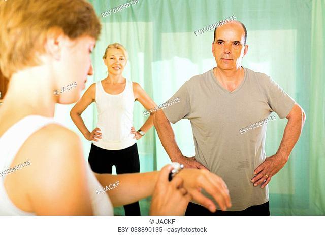 Female trainer keeping eye at training elderly couple in gym