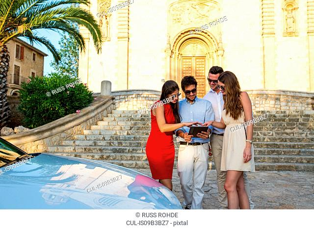 Two tourist couples looking at digital tablet by church, Calvia, Majorca, Spain