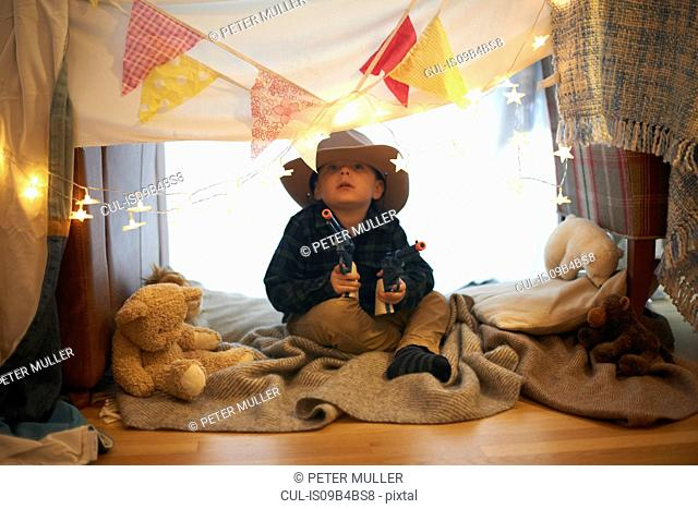 Portrait of cute boy in cowboy hat holding toy guns in bedroom den