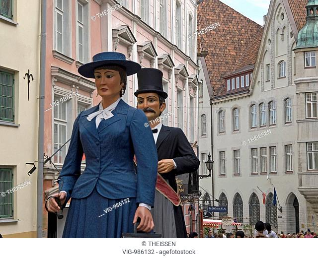 Catalonian festival with traditional festive procession with big figures of a man and woman in the streets of the old town of Tallinn, Estonia