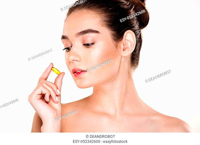 Beauty portrait of pretty concentrated woman with soft skin, holding pill in her hand posing over white background