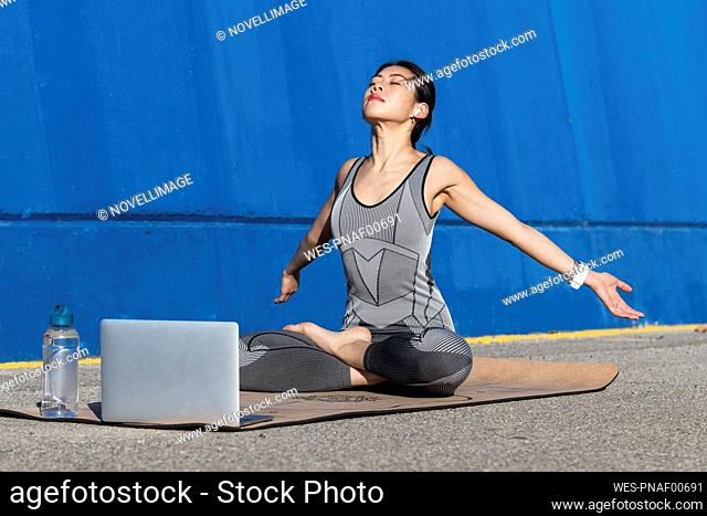 Woman with arms outstretched doing yoga in front of laptop