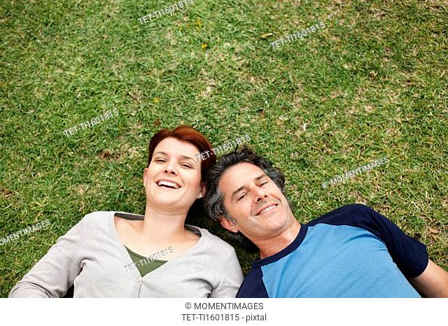 Happy couple relaxing on the grass together