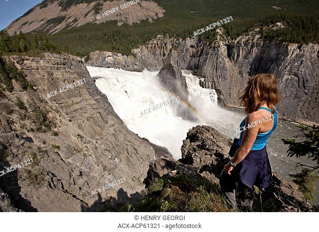 Woman enjoys view of Virginia Falls, Nahanni National Park Preserve, NWT, Canada