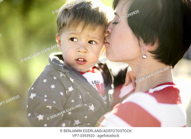 tender mother and son outdoors in park, sunny