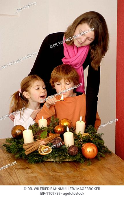 Young woman with children is lighting candles on an advent wreath