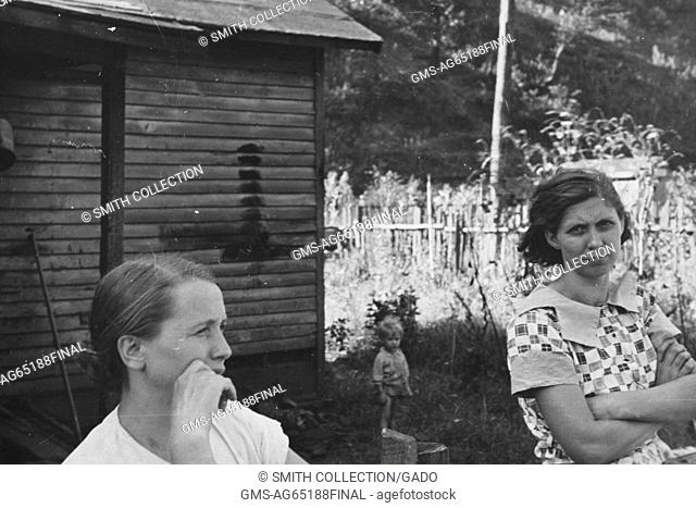 Two women and a small child, in a mining town, with a simple home, overgrown grass, and a roughly constructed wooden fence serving as the backdrop