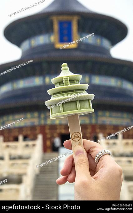 A tourist holds an ice cream in a shape of main temple building as visit Temple of Heaven in Beijing, China on 14/09/2021 An imperial complex of religious...