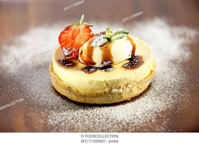 A mini cheesecake with cream and caramel sauce
