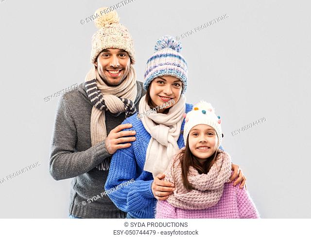 happy family in winter clothes on grey background