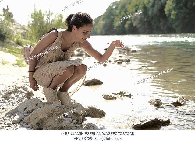 woman refreshing at riverside Isar in Munich, Germany